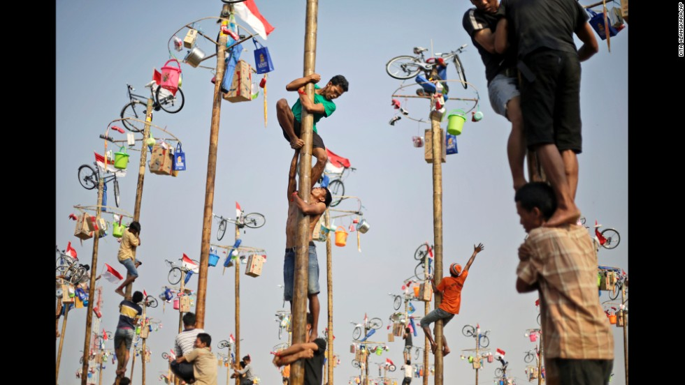 People in Jakarta, Indonesia, struggle to climb greased poles during a competition for prizes Sunday, August 17. It was part of Indonesia's Independence Day celebrations.