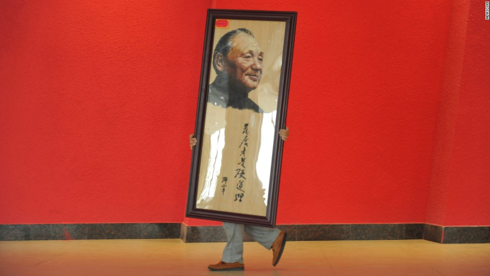 A worker moves a portrait of former Chinese leader Deng Xiaoping at an exhibition in Deng's hometown of Guangyuan, China, on Monday, August 18. The exhibition celebrated the 110th anniversary of the late leader's birth.
