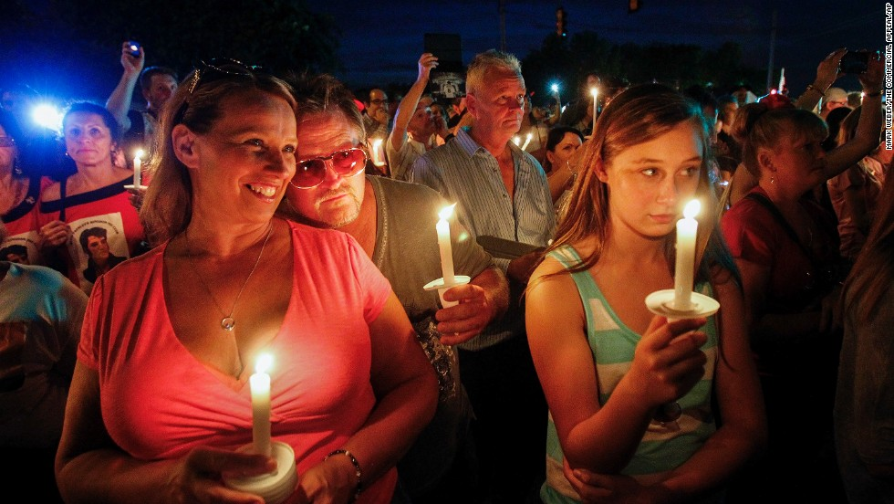 Sharon Kestner, left, enjoys the sounds of Elvis Presley during a candlelight vigil held Friday, August 15, outside the gates of Graceland, Presley's estate in Memphis, Tennessee. People gathered there in remembrance of Presley's death 37 years ago.