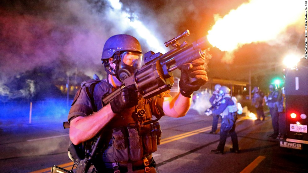 "A law enforcement officer fires tear gas in the direction where bottles were thrown from crowds Monday, August 18, in Ferguson, Missouri. The St. Louis suburb <a href=""http://www.cnn.com/2014/08/14/us/gallery/ferguson-missouri-protests/index.html"">has been in turmoil</a> since Darren Wilson, a white police officer, fatally shot Michael Brown, an unarmed black teenager, on August 9. Some protesters and law enforcement officers have clashed in the streets, leading to injuries and arrests."