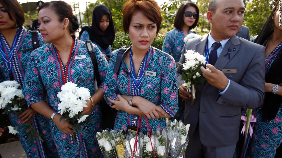 Malaysia Airlines' crew members held flowers as they waited for the plane's arrival. MH17 was shot down over eastern Ukraine on July 22, killing all 298 people on board.