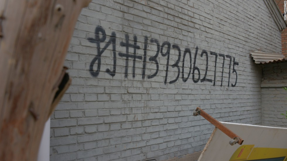 Graffiti on a wall, advertising well-digging services. A well can cost up to $6,500, according to residents.
