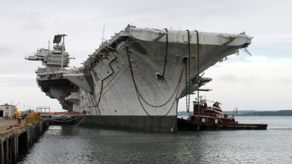 "In this photo released by the U.S. Navy, a tugboat works alongside the decommissioned aircraft carrier USS Saratoga on Thursday, August 21, in Newport, Rhode Island. The Navy has paid a Texas recycling company a penny to dispose of the Saratoga, part of the Forrestal-class of ""supercarrier"" vessels built for the Atomic Age. The carrier was decommissioned 20 years ago."