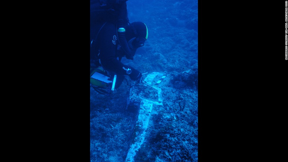 Greek archaeologist and fellow co-director of the dive, Theotokis Theodoulou inspects the 400-pound lead anchor stock of Antikythera Wreck B, found last year at one end of the debris field during a preparatory dive. The other end of the wreck is signaled over 50 meters away by roof tiles believed to be from the galley structure at the stern of the ship. Based on this evidence, scientists estimate the vessel to be one of the largest ships from antiquity, making it bigger than some of the most colossal boats known from that time -- Caligula's pleasure barges on Italy's Lake Nemi.
