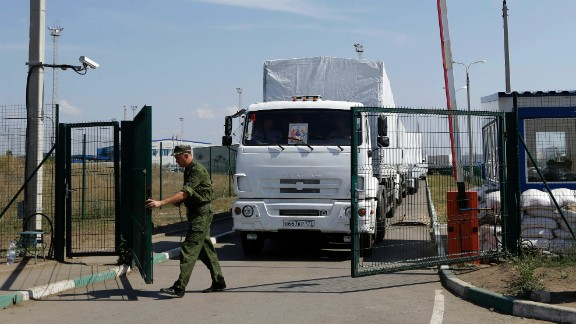 A Russian border guard opens a gate into the Ukraine for the first trucks heading into the country from the Russian town of Donetsk, Rostov-on-Don region, Russia, Friday, Aug. 22, 2014. The first trucks in a Russian aid convoy crossed into eastern Ukraine on Friday, seemingly without Kiev's approval, after more than a week's delay amid suspicions the mission was being used as a cover for an invasion by Moscow.(AP Photo/Sergei Grits)