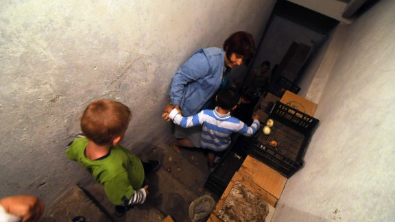 Children are taken into the cellar of an orphanage for shelter during intense shelling in Marynivka, Ukraine, on August 19. Photojournalist Jonathan Alpeyrie spent the day with locals, going in and out of bomb shelters as missiles were launched on the city.