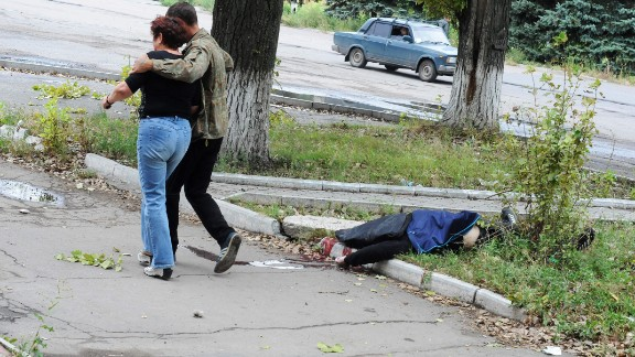 """Residents walk past a victim of the rocket attacks. """"People do get killed. If you're walking down the street it's like a lottery, you just don't know,"""" Alpeyrie says."""