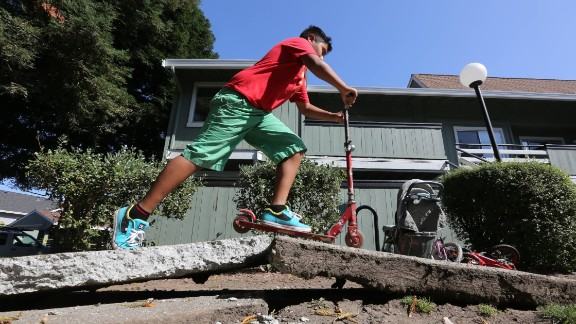 A boy rides a scooter over a sidewalk buckled by the earthquake on August 24 in Napa.