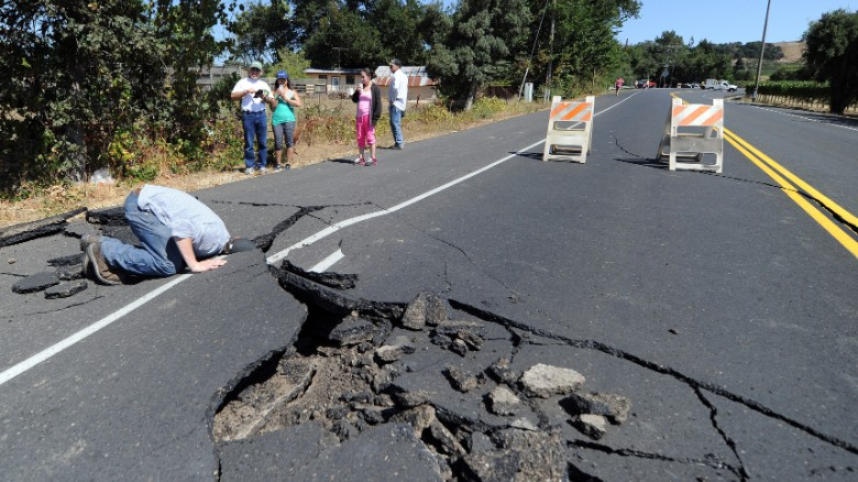 Nicholas George looks under a buckled highway just outside of Napa, California after earthquake struck the area in the early hours of Sunday August 24.