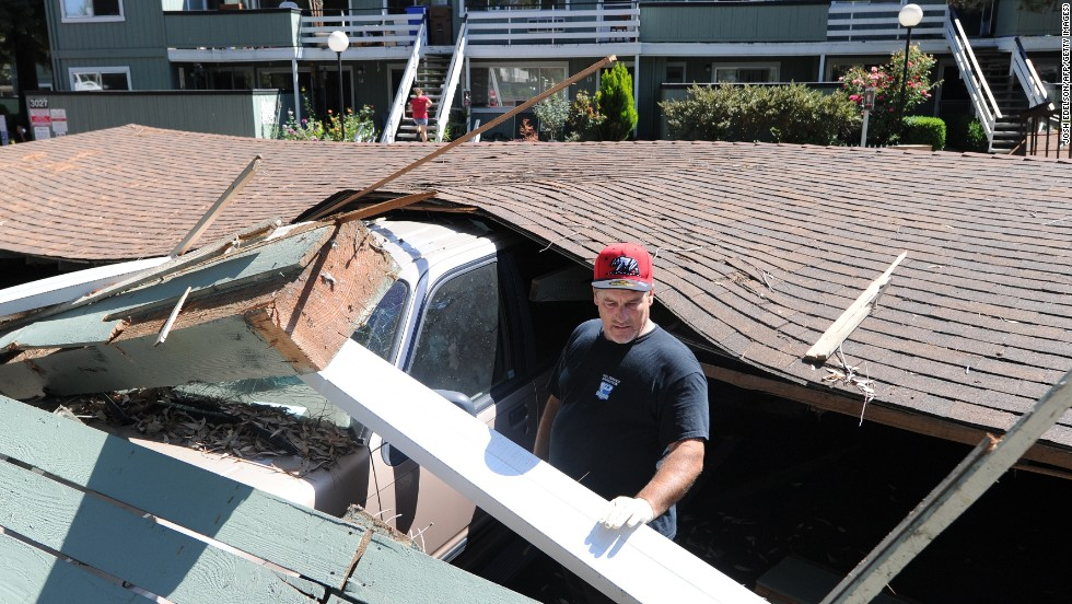 Karl Luchsinger attempts to disentangle his daughter's car on August 24 after the car port it was parked in collapsed in Napa.