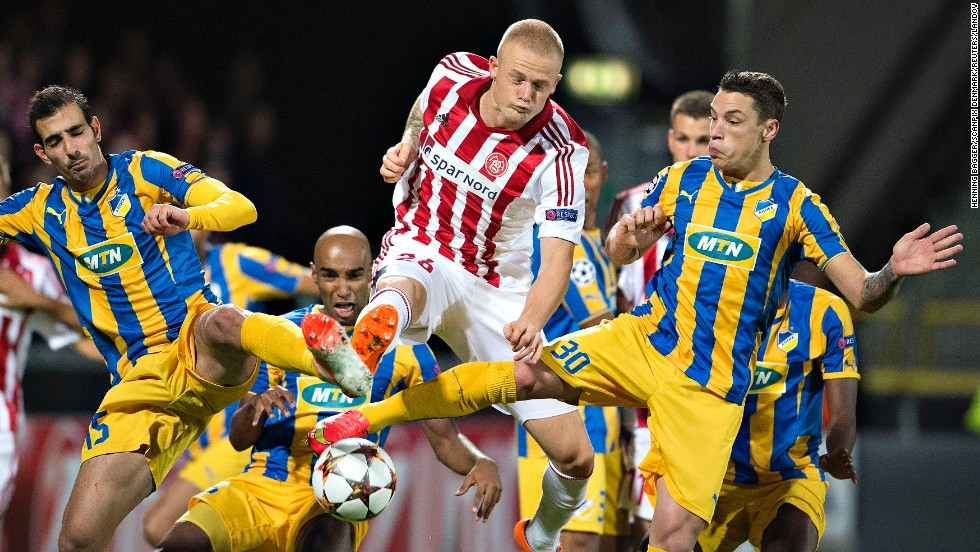 Rasmus Thelander, center, of Denmark's Aab Aalborg, fights for the ball between Marios Antoniades and Tomas De Vincenti, both of Cyprus' Apoel Nicosia, during a Champions League playoff match in Aalborg, Denmark, on Wednesday, August 20. The game ended 1-1.