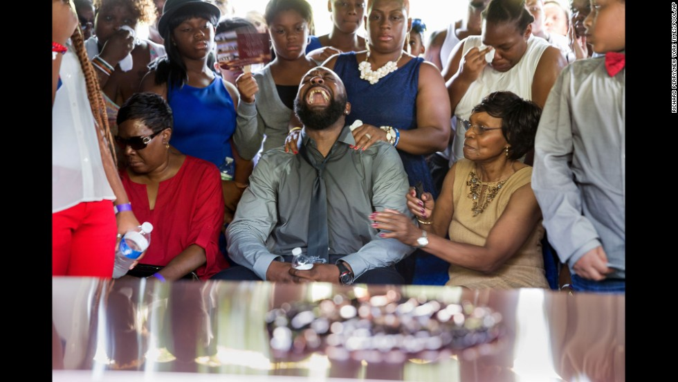 Michael Brown Sr. yells out as the casket holding the body of his son, Michael Brown, is lowered into the ground during his funeral service in St. Louis.