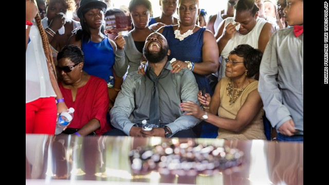 Michael Brown Sr., yells out as the casket holding the body of his son, Michael Brown, is lowered into the ground during the funeral service in Normandy, Missouri, on Monday, August 25.
