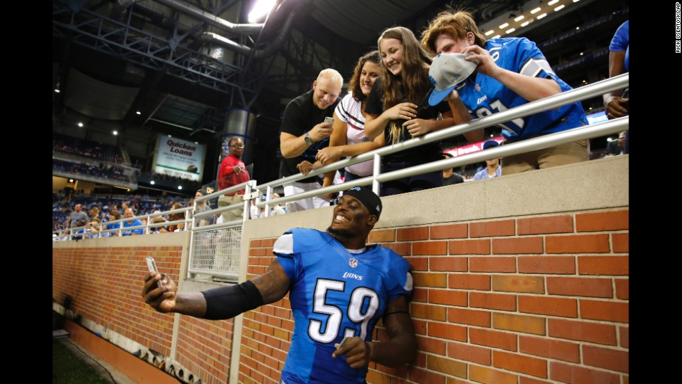 Detroit Lions linebacker Tahir Whitehead shoots a selfie with fans after a preseason NFL football game against the Jacksonville Jaguars at Ford Field in Detroit on Friday, August 22.
