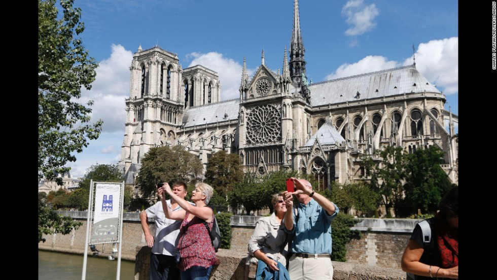 Tourists take selfies outside Notre Dame Cathedral in Paris on Friday, August 22.  About 13 million tourists visit the cathedral each year, according to its website.