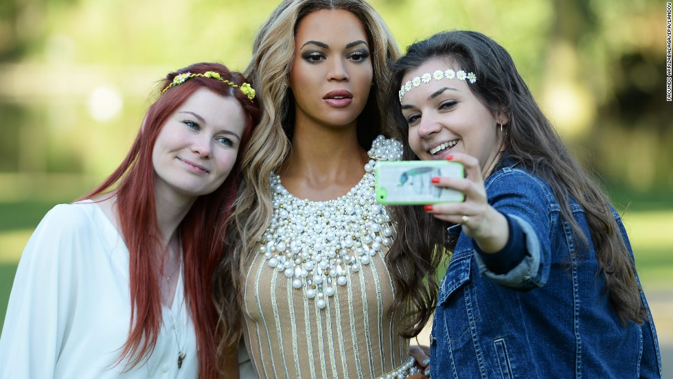 Two Madame Tussauds employees take a selfie with a wax figure of U.S. singer Beyonce during a photo call near the Regents Park bandstand in London on Wednesday, August 20. Beyonce was the recipient of the the Michael Jackson Video Vanguard Award at this year's MTV Video Music Awards.