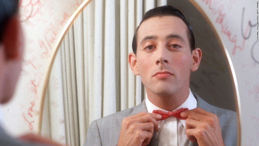 Beloved performer Pee-wee Herman, here circa 1980, straightens his characteristic red bow tie, which he always pairs with a light gray suit.