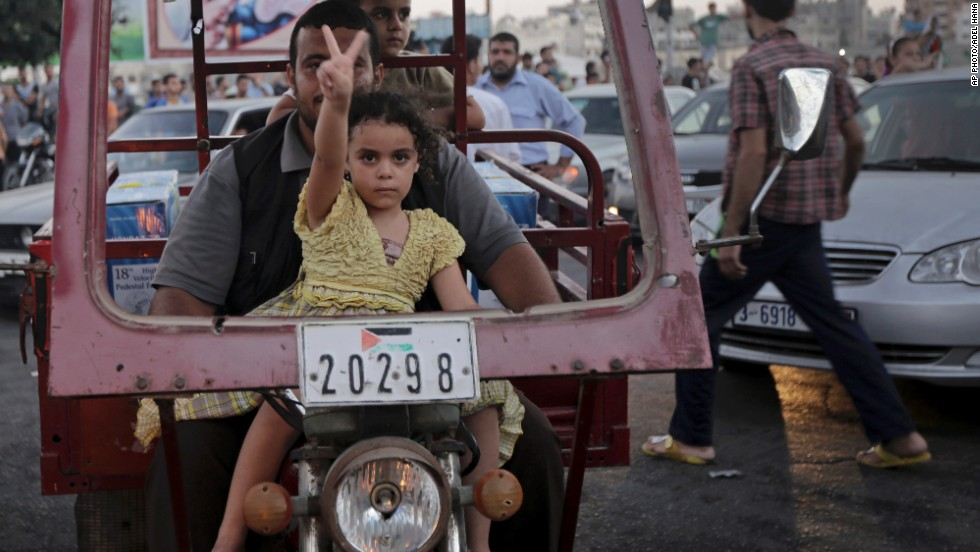 "AUGUST 27 - GAZA: A little girl flashes a victory sign as Palestinians in Gaza celebrate the truce with Israel. After more than seven weeks of heavy fighting, <a href=""http://edition.preview.cnn.com/2014/08/27/world/meast/mideast-crisis/index.html?hpt=hp_t2"">the two sides have agreed to an open-ended ceasefire</a>."