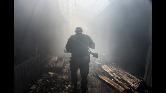 A pro-Russian rebel walks through a local market damaged by shelling in Donetsk on Tuesday, August 26.