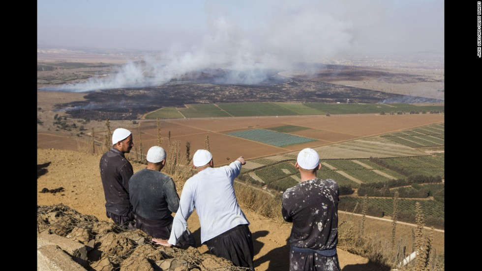 Druze men watch from the Golan Heights side of the Quneitra border with Syria as smoke rises during fighting between rebels and forces loyal to al-Assad on Wednesday, August 27.