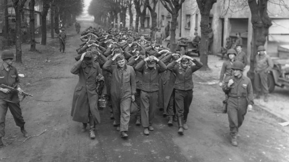 German prisoners captured at Friedrichsfeld march through a town in Germany after the crossing of the Rhine River by the U.S. 9th Army on March 26, 1945.