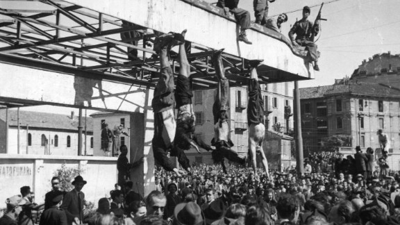 The bodies of Benito Mussolini, left, and his mistress, Clara Petacci, second from left, hang from the roof of a gasoline station after they were shot by anti-Fascist forces while attempting to escape to Switzerland on April 28, 1945.