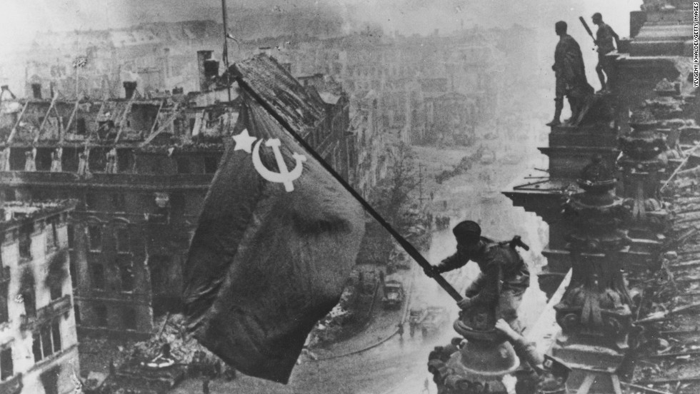 Russian soldiers wave their flag, made from tablecloths, over the ruins of the Reichstag in Berlin on April 30, 1945. That day, as the Soviets were within blocks of his bunker at the Reich Chancellery, Adolf Hitler committed suicide.