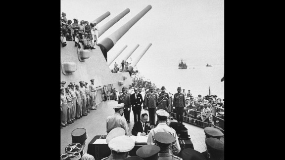 Japanese Foreign Minister Mamoru Shigemitsu signs the Japanese Instrument of Surrender on the deck of the battleship USS Missouri in Tokyo Bay on September 2, 1945, officially bringing World War II to an end. Overseeing the surrender is U.S. Gen. Douglas McArthur (right, back to camera).