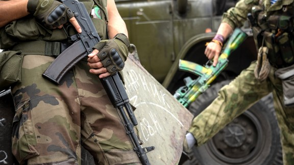 Pro-Russian rebels hold their guns as they patrol the Lenin square in the town of Donetsk, eastern Ukraine, Thursday, Aug. 28, 2014. Ukraine