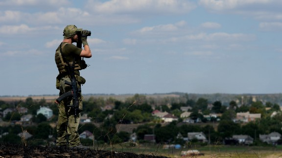 A Ukrainian loyalist fighter from the Azov Battalion stands guard on a hill on the outskirts of Mariupol on August 30.