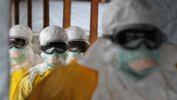 Health care workers, wearing protective suits, leave a high-risk area at the French NGO Medecins Sans Frontieres (Doctors without borders) Elwa hospital on August 30, 2014 in Monrovia.