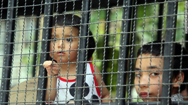 Asylum seekers, including children, are transported by immigration officials to a court in southern Thailand on March 15.