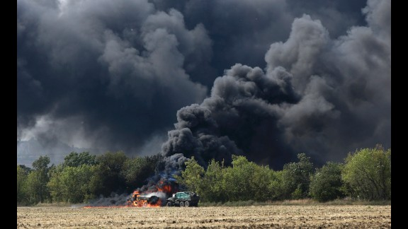 Unmarked military vehicles burn on a country road in Berezove, Ukraine, on September 4 after a clash between Ukrainian troops and pro-Russian rebels. For months, Ukrainian government forces have been fighting the rebels near Ukraine's eastern border with Russia.