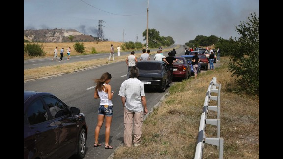 People wait by their cars near Berezove on September 4 as rockets hit the road ahead.