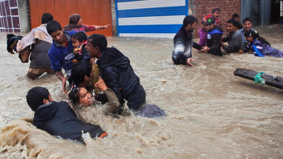 People struggle to pass through floodwaters Thursday, September 4, in Srinagar.