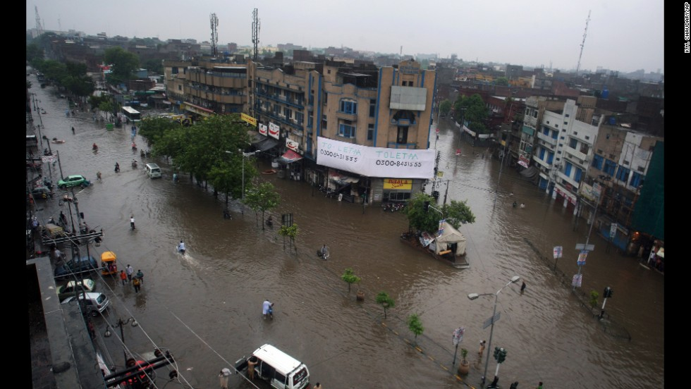 Motorcycles and vehicles move through flooded streets in Lahore on September 4.