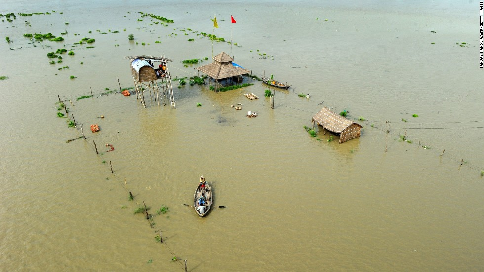 People flee submerged huts on the flooded banks of the Ganga on Friday, August 8.