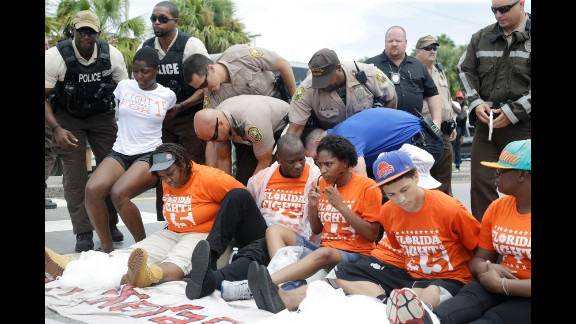 Police officers arrest a group of demonstrators that were blocking a road in North Miami Beach, Florida, on September 4.