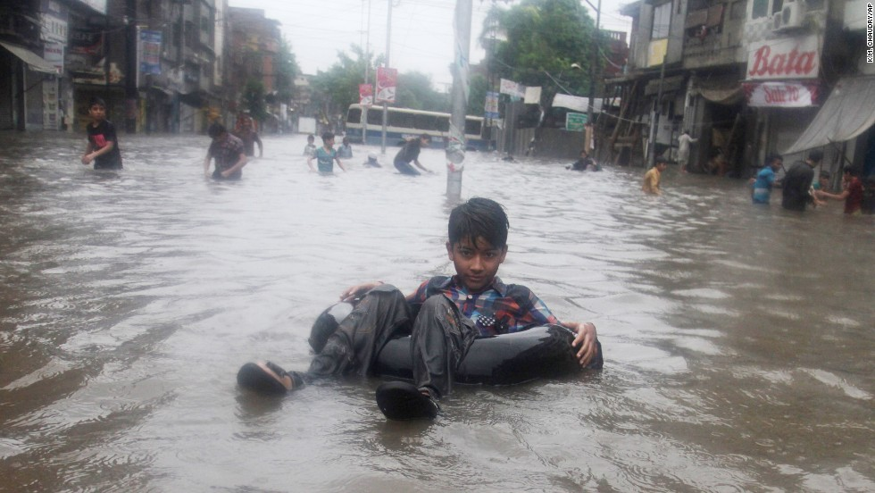 Children play in a road flooded by heavy rains in Lahore, Pakistan, on Friday, September 5.
