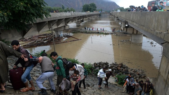 Kashmiri residents walk along an embankment on the side of a bridge as they head for a higher ground on the outskirts of Srinagar, India on  Saturday, September 6.