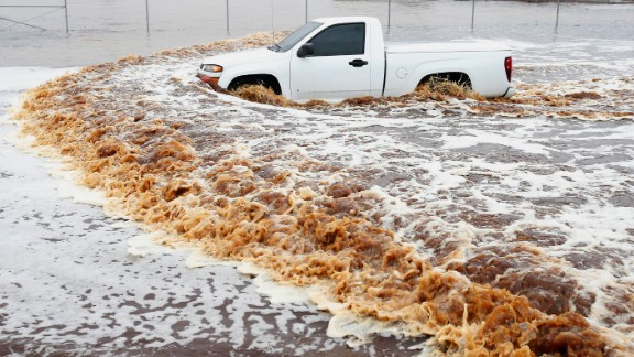 A truck creates a wake as its driver tries to make it through a severely flooded street in Phoenix on Monday, September 8. Arizona's governor declared a statewide emergency as record-setting rains flooded numerous Phoenix-area roadways and forced some schools to shut down.