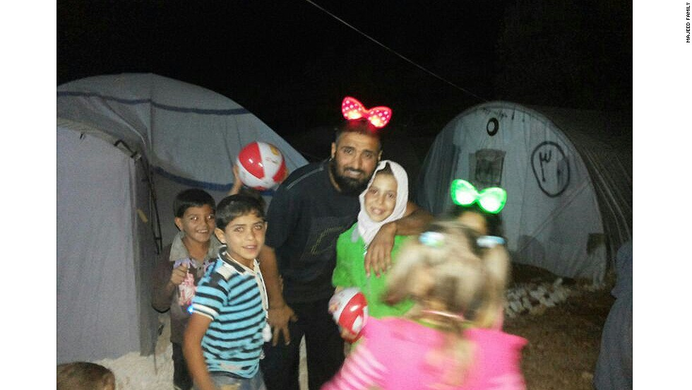 In one photo, Majeed wears Minnie Mouse ears in an apparent attempt to brighten the lives of the children in the refugee camps of northern Syria.