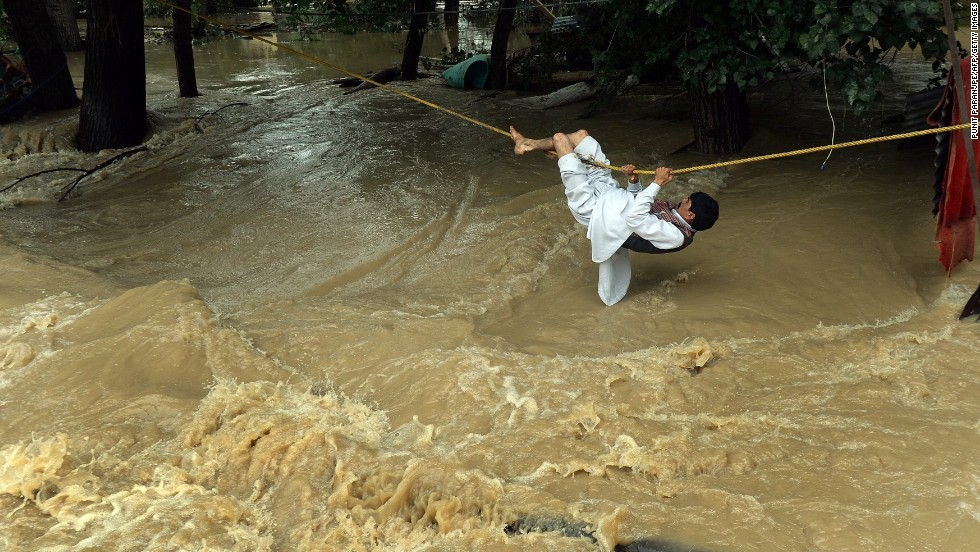 A man crosses over floodwaters with the use of a rope Tuesday, September 9, in Srinagar.
