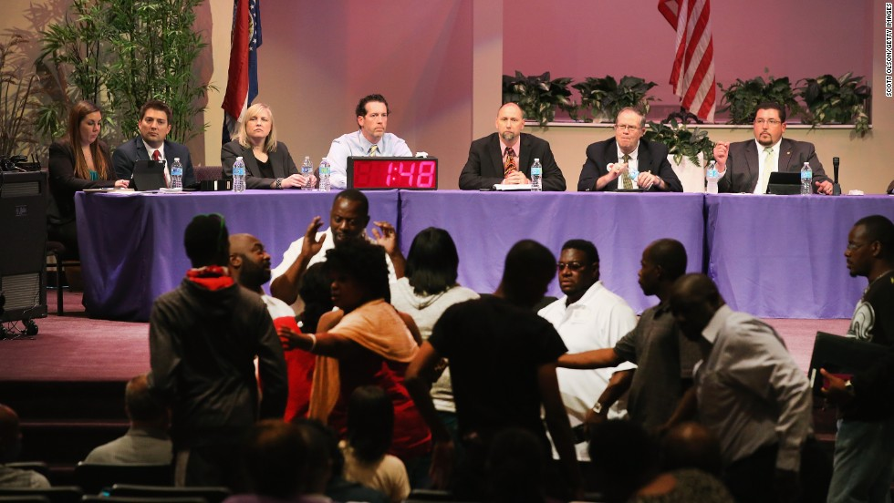 Mayor James Knowles, seated right, and council members wait for angry residents to calm down during a City Council meeting in Ferguson, Missouri, on Tuesday, September 9. The meeting was held at Greater Grace Church to accommodate the large crowd. Residents used the meeting to express their anger at how the police and council handled the August 9 shooting of teenager Michael Brown and the unrest that followed.