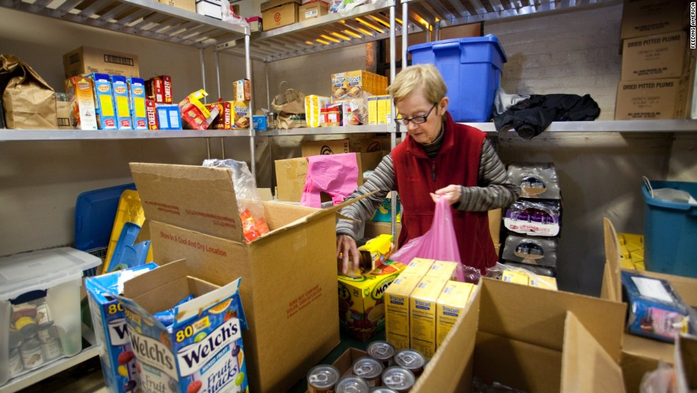 "A <a href=""http://feedingamerica.org/"" target=""_blank"">Feeding America</a> volunteer packs a bag of groceries for a family in need. She is one of nearly 2 million volunteers who, combined, contribute more than 8.4 million hours of time every month to the organization."