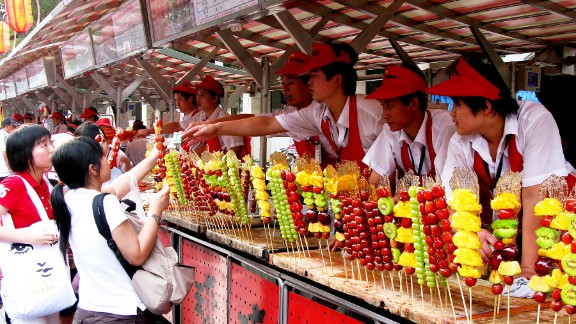 Skewers of sweet pineapple, tart green grapes, and other colorful arrangements of fruit line a concession stand in Beijing, China.