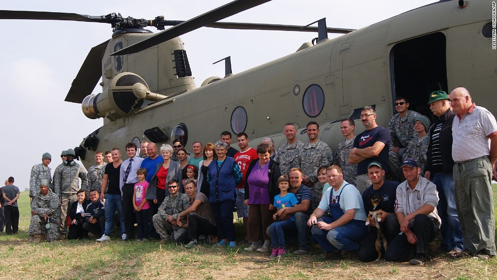 Residents of the village of Gruta, in northern Poland, pose for a photo with U.S. troops and their Chinook helicopter in the middle of a village field where six U.S. Army helicopters made an unplanned landing in poor weather on Tuesday, September 9.