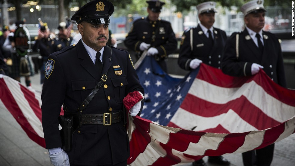 Members of the New York Police Department, the New York Fire Department and the Port Authority Police Department carry an American flag past one of the reflecting pools during memorial observances at the World Trade Center site.