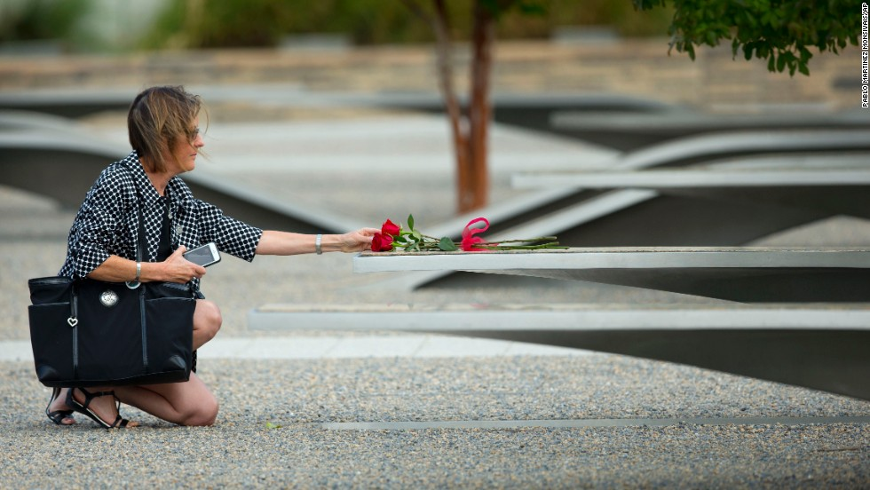 A woman reaches out to touch a rose on one of the benches at the Pentagon Memorial.