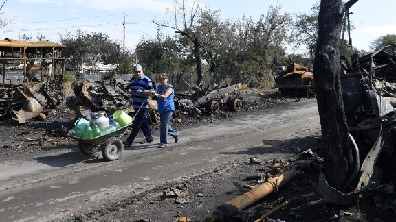 Residents of Lutuhyne, Ukraine, push containers in a wheelbarrow September 11 as they walk between destroyed armored vehicles left behind by the Ukrainian army.